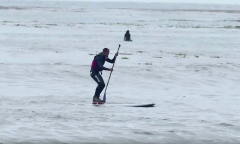 Tyler Fox, attempting to paddle board while on roller skates.