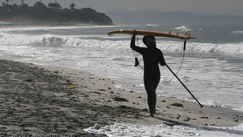 Rhonda Daum taking a walk down the beach after a Cardiff Reef surf session on her stand up paddle board.