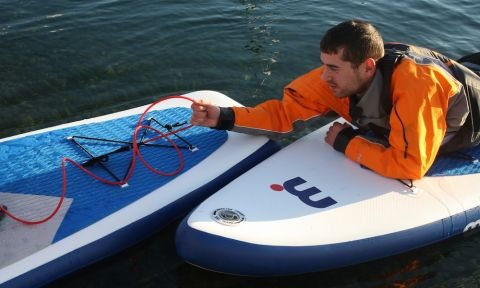 A simple way to set up a tow for a paddler in need is for them to hold onto the leash of the person towing.