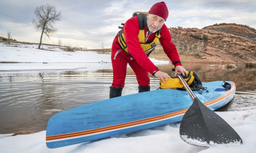 Senior male paddler in drysuit and a racing stand up paddle board on lake in Colorado. | Photo Courtesy: Shutterstock