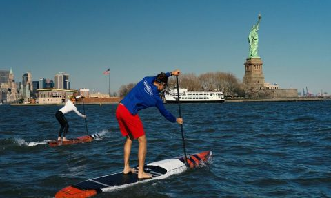 Candice Applebee and unidentified paddler in NYC with the Statue of Liberty in the distance. | Photo: APP / Matt Gunther