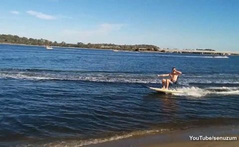 Man Swigs Beer While Being Towed On Paddleboard